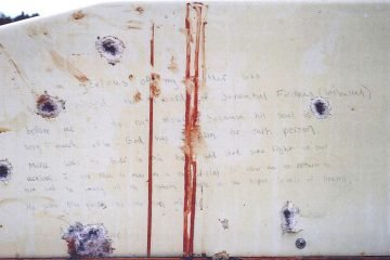 This undated forensics photograph provided by the U.S. Attorney's office and presented as evidence during the federal death penalty trial of Boston Marathon bombing suspect Dzhokhar Tsarnaev Tuesday, March 10, 2015, in Boston, shows handwriting on the bullet-riddled, blood-stained wall of a boat. The prosecution presented the photo as evidence of the handwritten note found inside the boat where Tsarnaev was captured April 19, 2013 in Watertown, Mass., four days after the bombings. (AP Photo/U.S. Attorney's Office)